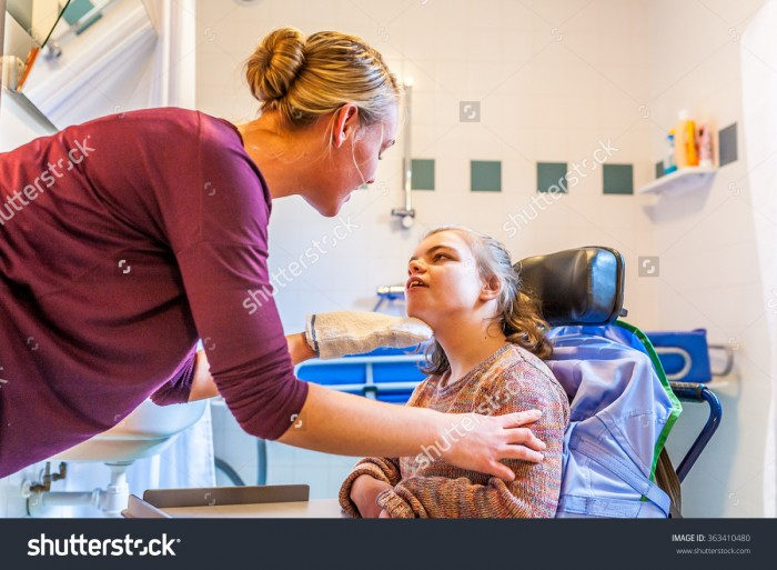 stock-photo-disabled-child-in-a-wheelchair-being-cared-for-by-a-special-needs-nurse-working-with-disability-363410480